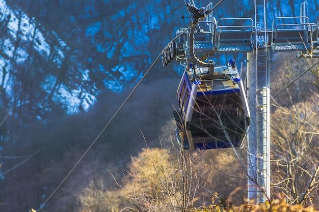 谷の背景に霧があるスキーヤーのためのスキーリフトケーブルロープウェイとケーブルウェイ輸送システム