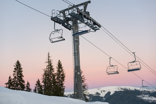 Ski lift chairs on winter resort against a beautiful sky at sunset