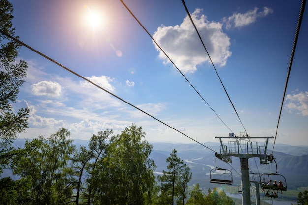 青い空、白い雲、緑の丘、山の湖に対して晴れた日に山でスキー場のリフト。ケーブルカーのあるマウンテンバレー、上からの眺め。夏のスキーリゾート。