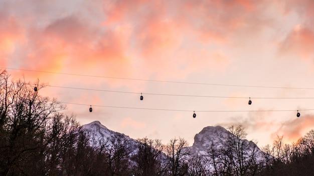 Подъемник в горы силуэт против драматического неба