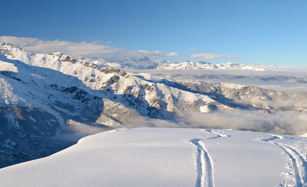 Ski path in powder snow, winter landscape in the alps