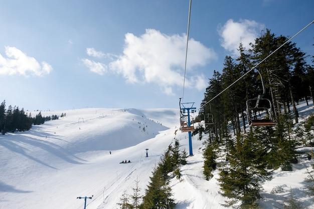 晴れた日には雪に覆われた木々とスキーゲレンデとチェアリフト。コンブルースキー場、フランスアルプス