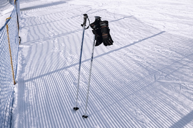 Ski poles with gloves near ski pistes