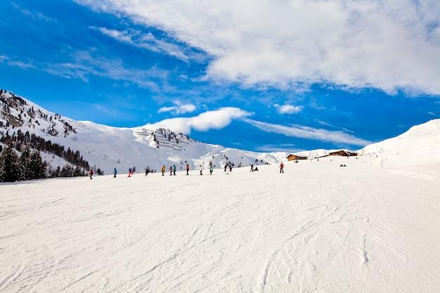 Горнолыжный курорт в альпах. панорамный вид на горы. люди катаются на лыжах и сноуборде. майерхофен, австрия