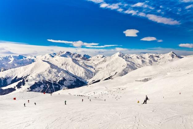 アルプスのスキーリゾート。山々のパノラマビュー。オーストリア、マイヤーホーフェンでスキーをする人々
