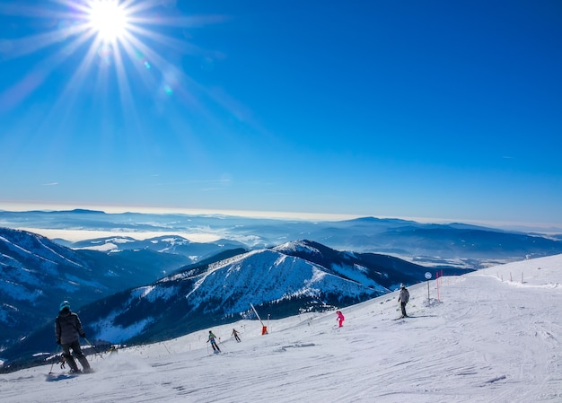 Ski resort jasna in winter slovakia. panoramic view from the top of the snow-capped mountains and ski slope with skiers