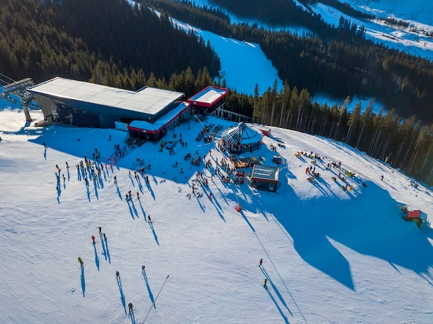 Ski resort in sunny weather. snow on the ski slope of a wooded mountain. many tourists near the ski lift station and cafe. aerial view