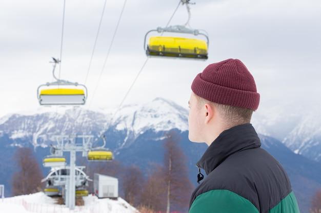 スキーリゾート。若い男は自然を賞賛し、山に立ち向かいます。