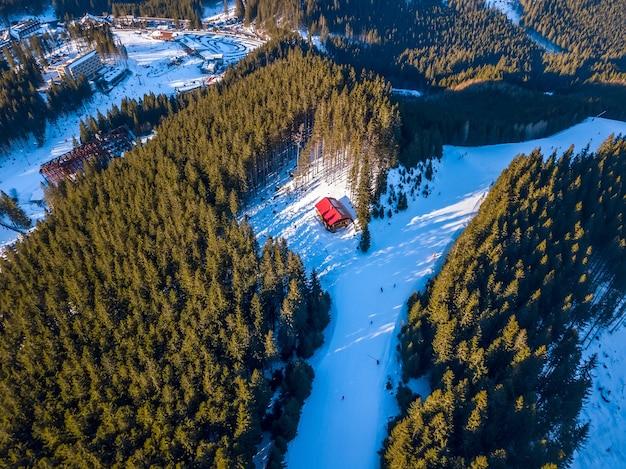 樹木が茂った山々のスキー場。ホテルや駐車場のある谷。晴天。航空写真