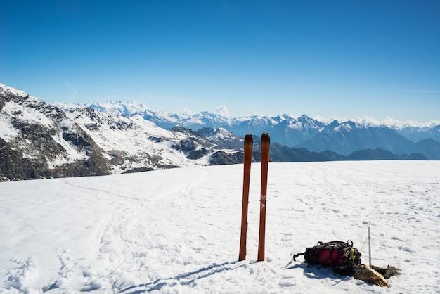 Ski tour equipment on the summit, majestic mountain range