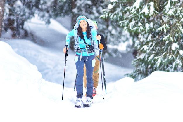 눈이 내리는 동안 숲에서 스키 투어링. 행복한 소녀