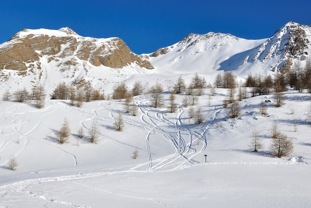 Ski tracks zigzagging on the slope in snowy mountain and under blue sky