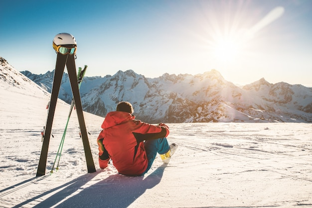 Skier athlete sitting in snow mountains on sunny day - adult man enjoying the sunset with skies gear next to him - winter sport and vacation concept - focus on male body