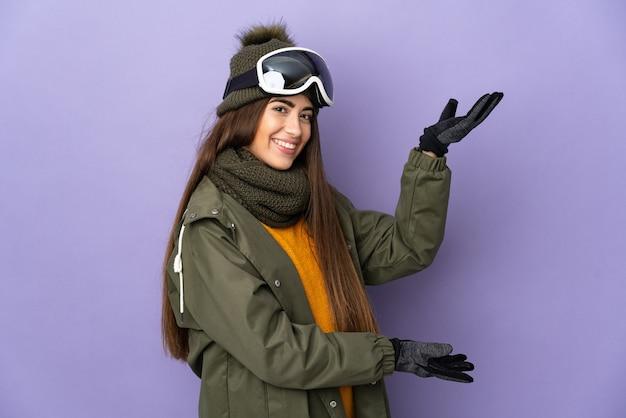 와 서 초대를 위해 손을 옆으로 확장 보라색 배경에 고립 된 스노우 보드 안경 스키 백인 여자