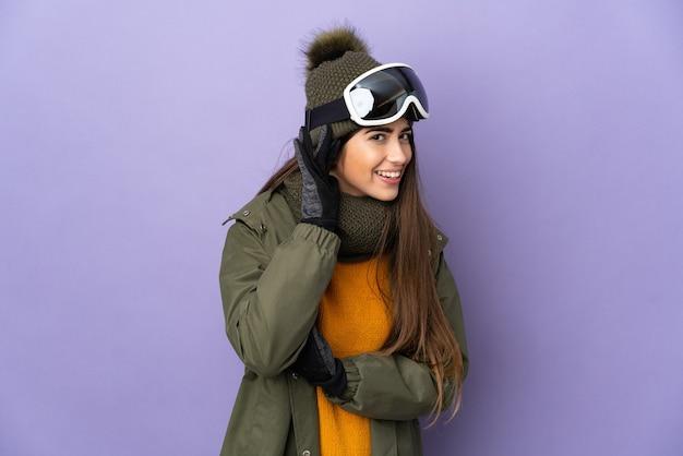 스노우 보드 안경 스키 백인 여자는 귀에 손을 넣어 뭔가를 듣고 보라색 배경에 고립