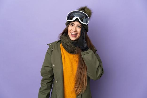 입 벌리고 외치는 보라색 배경에 고립 된 스노우 보드 안경 스키 백인 여자