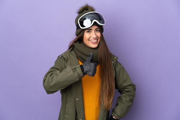 Кавказская девушка-лыжница в очках для сноуборда изолирована на фиолетовой стене, показывая большой палец вверх
