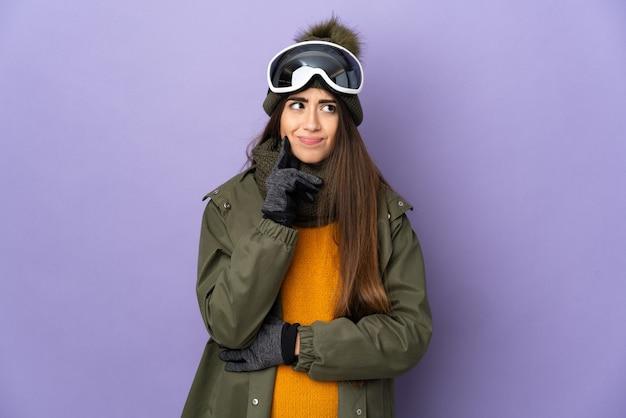 의심과 생각을 갖는 보라색 벽에 고립 된 스노우 보드 안경 스키 백인 여자