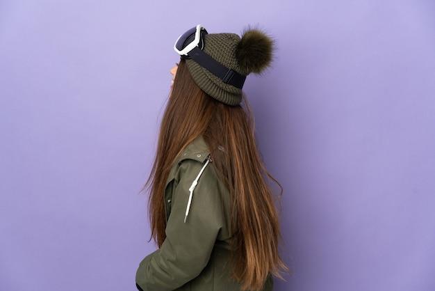 Кавказская девушка лыжника в очках для сноуборда изолирована на фиолетовой стене, смеясь в боковом положении