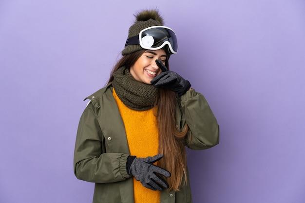 Кавказская девушка лыжника в очках для сноуборда изолирована на фиолетовой стене смеясь