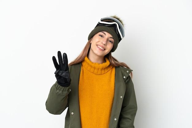 Кавказская женщина лыжника в очках для сноуборда на белом фоне счастлива и считает три пальцами