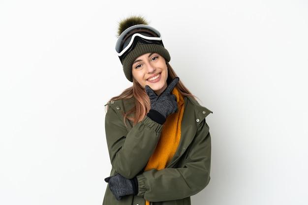幸せと笑顔の白い背景で隔離スノーボードメガネとスキーヤー白人女性