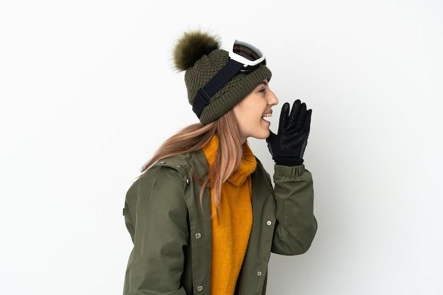 横に大きく開いた口で叫んで白い背景に分離されたスノーボードグラスを持つスキーヤー白人女性