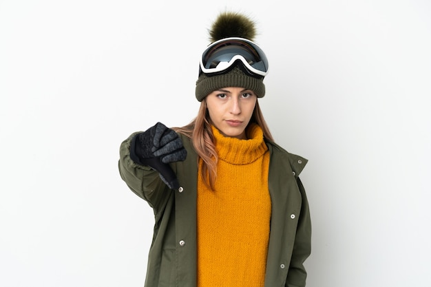否定的な表現で親指を示す白い背景に分離されたスノーボードグラスを持つスキーヤー白人女性