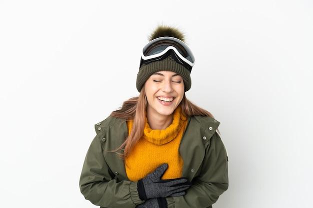 Кавказская женщина лыжник в очках для сноуборда на белом фоне много улыбается