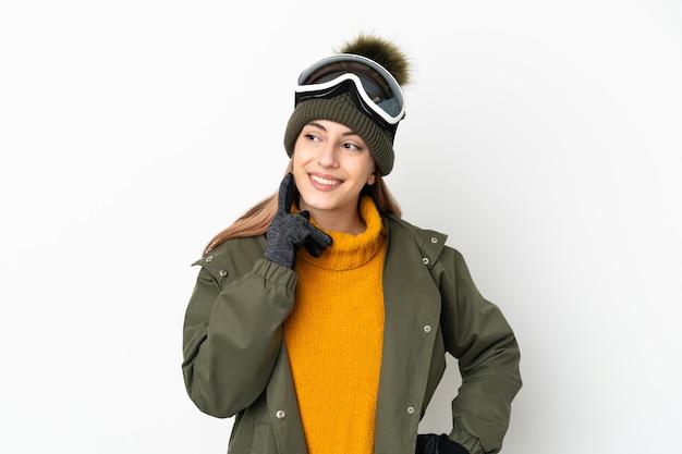 Кавказская женщина лыжника в очках для сноуборда изолирована на белом фоне, думая об идее, глядя вверх