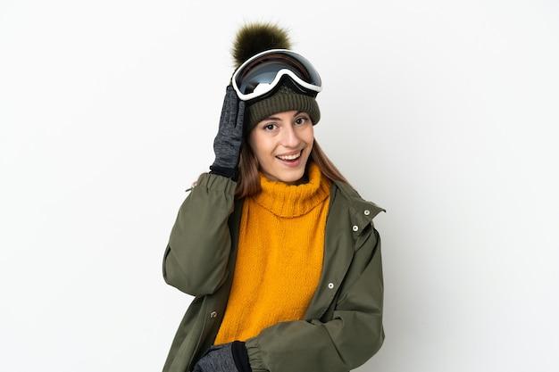 Кавказская женщина-лыжница в очках для сноуборда изолирована на белом фоне с удивлением и шокированным выражением лица