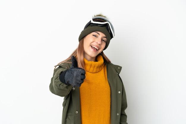 何か良いことが起こったので、親指を上にして白い背景で隔離のスノーボードグラスを持つスキーヤー白人女性