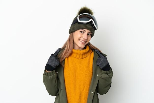 親指を立てるジェスチャーを与える白で隔離のスノーボードグラスを持つスキーヤー白人女性