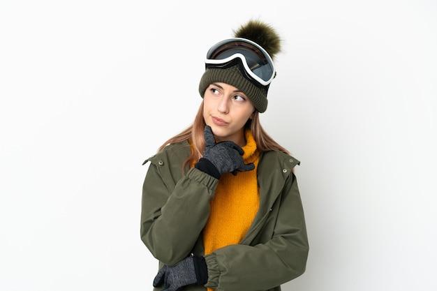 Кавказская женщина лыжника в очках для сноуборда изолирована на белой стене и смотрит вверх