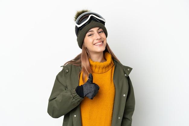 Кавказская женщина-лыжница в очках для сноуборда изолирована на белой стене, показывая жест рукой вверх