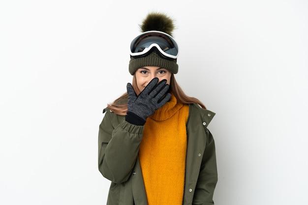 Кавказская женщина-лыжница в очках для сноуборда изолирована на белой стене, счастливая и улыбающаяся, прикрывая рот рукой