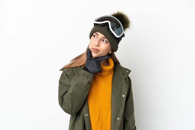 Кавказская женщина лыжника в очках для сноубординга изолирована на белой стене, сомневаясь