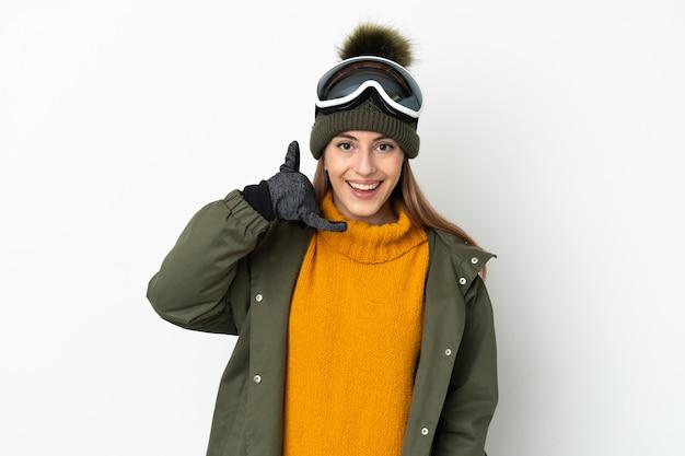 Женщина лыжника кавказская с очками сноубординга изолированными на белой стене делая жест телефона. перезвони мне знак
