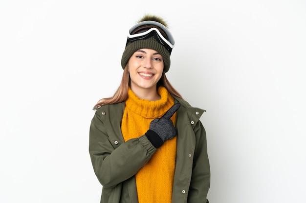 Кавказская женщина-лыжница в очках для сноуборда изолирована на белой стене, указывая в сторону, чтобы представить продукт