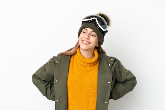흰 벽 엉덩이에 팔을 포즈와 미소에 고립 된 스노우 보드 안경 스키 백인 여자