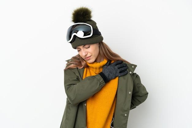 Кавказская женщина-лыжница в очках для сноуборда изолирована на белой стене и страдает от боли в плече за то, что приложила усилие
