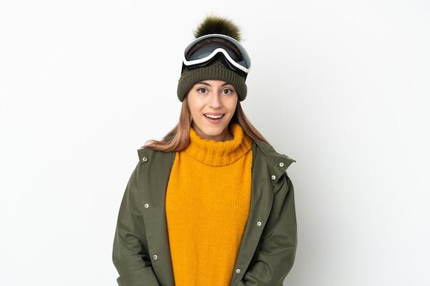 Кавказская женщина-лыжница в очках для сноуборда изолирована на белой стене с удивленным выражением лица