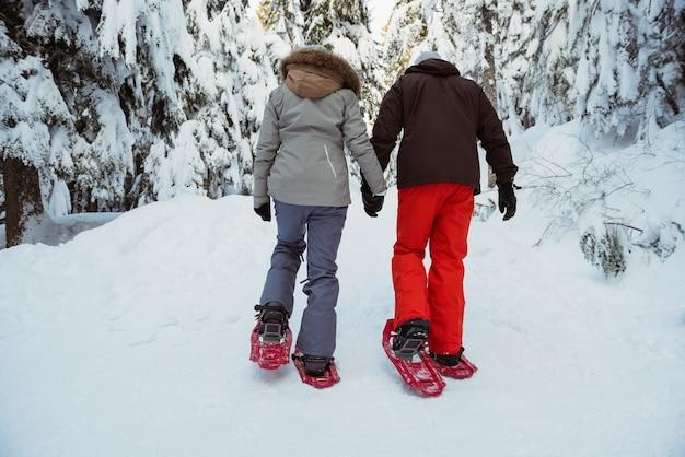 雪に覆われた山の上を歩くスキーヤーのカップル