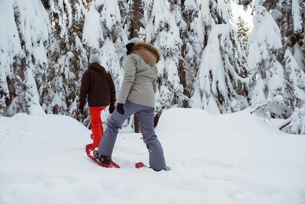 雪山を歩くスキーヤーカップル
