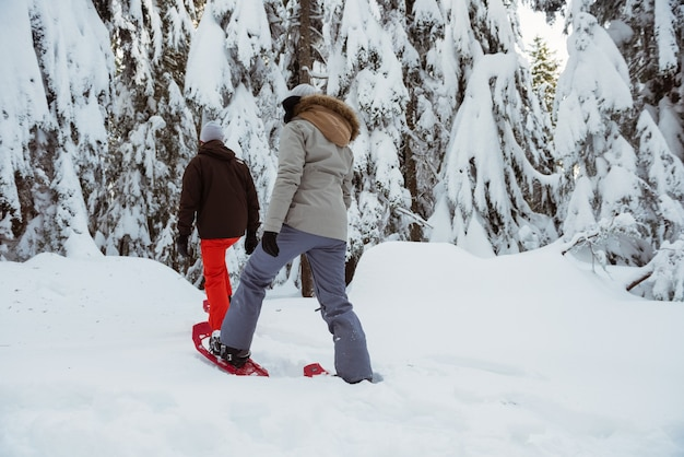Skier couple walking on snowy mountain