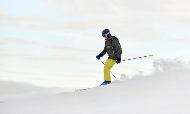 雪に覆われた高山の頂上から降りるスキーヤー