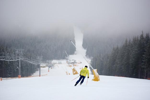 密な針葉樹林の中でチェアリフトを使って山の斜面の降雪でフリーライディング降下をしているスキーヤー。背面図