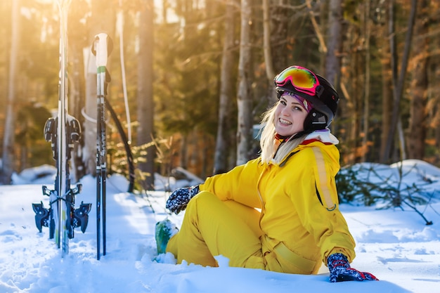Skier girl resting on the top of the mountain