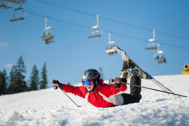 Skier girl in ski goggles lying with raised arms on snowy slope at mountain top in sunny day