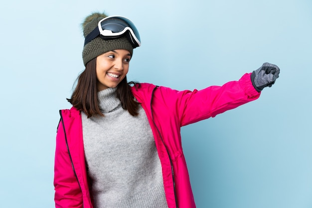 Skier girl with snowboarding glasses over isolated giving a thumbs-up gesture